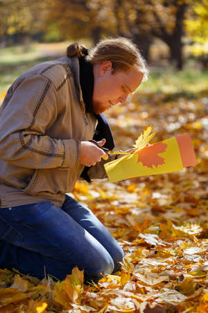 spangled: Young red-haired man sitting on the ground spangled with leaves in autumn park cutting maple leaves of colored paper by scissors and making them real by his imagination