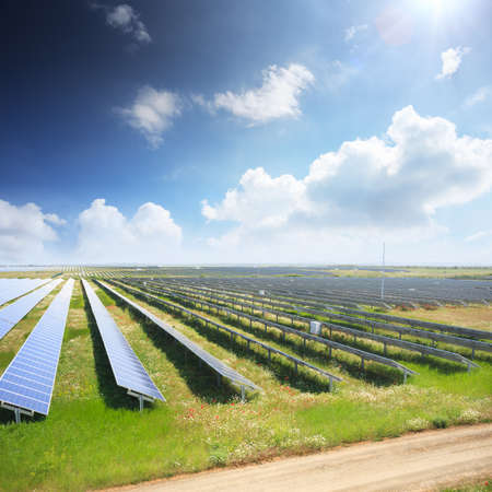 clean energy: Solar panels with green field and country road