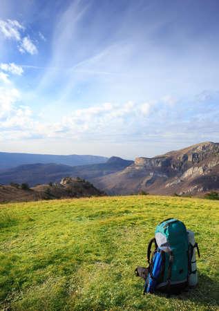 mochila de viaje: Mochila de viaje de pie en la hierba verde sobre un fondo de monta�as bajo el cielo nublado azul Foto de archivo