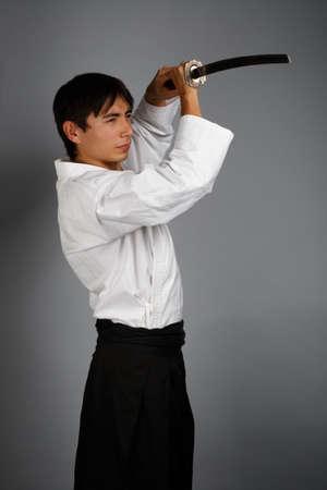 katana sword: Bellicose man on grey background standing in fighting pose with katana sword
