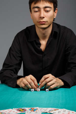 gambler: Young gambler man in black shirt sitting at the playing table isolated on black background