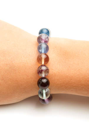 fluorite: Beautiful bracelet made of colorful fluorite round beads on elegant female hand isolated on white background. Close up. Stock Photo