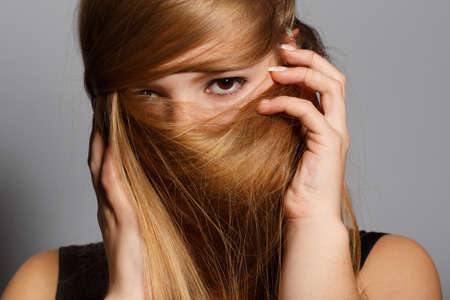 eloquent: Beautiful young woman hiding her face under the long blonde hair on grey background
