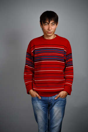 unworried: Man in striped red sweater standing isolated on grey background and limply smiling