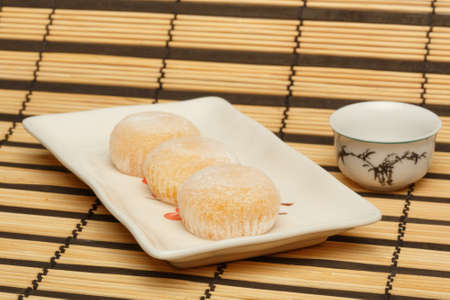 asian foods: Three delicious japanese mochi rice cakes on white plate standing on striped bamboo mat background with white porcelain cup. Shallow dof. Focus on first cake.