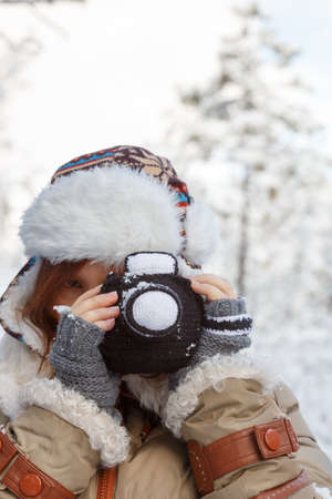 Beautiful young woman in winter clothing, fingerless mittens and ornamented hat photographing snowy forest by a knitted camera. Shallow dof. Focus on hands and camera. 스톡 콘텐츠