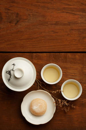 porcelain flower: Delicious japanese mochi rice cake on white plate, gaiwan and white porcelain cups with green tea standing on brown wooden surface decorated with dried flower. Stock Photo