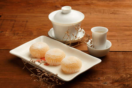 Delicious japanese mochi rice cakes on white plate, gaiwan and white porcelain cups with green tea standing on brown wooden surface decorated with dried flower.