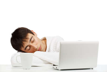 netbook: Young man in white sweater sleeping at the netbook isolated on white background Stock Photo