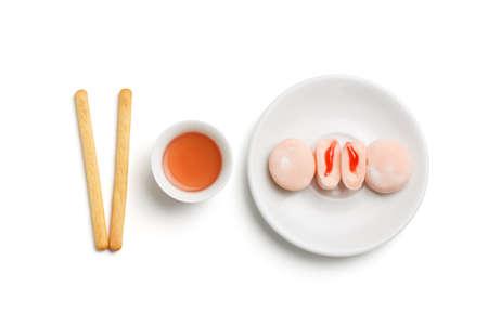 comida japonesa: Diseño de la comida minimalista con la taza de té rojo chino, pasteles de frutas de color rosa de pie en la placa de porcelana y galletas galletas palos aislados sobre fondo blanco. Foto de archivo