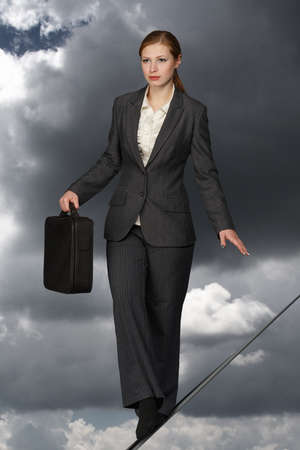 Business woman with case balancing on rope. Stock Photo