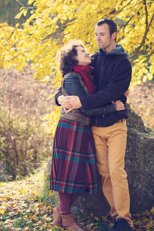 infatuation: Loving couple in bright clothes hugging in autumnal park