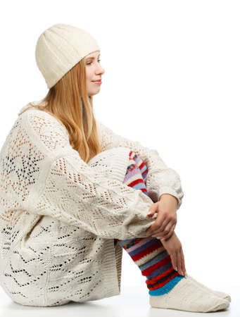 gaiters: Young beautiful smiling woman with long blonde hair siting in white knitted sweater, cap and striped gaiters isolated on white background in hugging knees pose