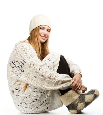 siting: Young beautiful woman siting in white sweater and cap isolated on white background