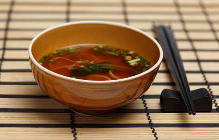 dashi: Miso soup in brown bowl standing on bamboo mat with back chopsticks lying near.