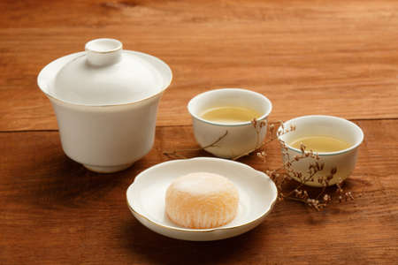 porcelain flower: Gaiwan and cups of white chinese porcelain with green tea standing on wooden table with delicious japanese mochi rice cake on white plate, decorated with dried flower.