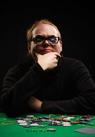 his shirt sleeves: Beautiful young red-haired man in glasses and shirt with long sleeves sitting at poker table with cards and chips on it inserting two chips before his eyes at black background.