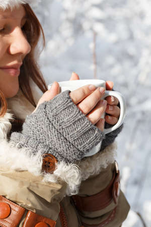Beautiful young smiling woman in gray fingerless knitted mittens, cap and coat with white fur holding in hands white cup of tea or coffee at the background of snowy forest. Closeup.