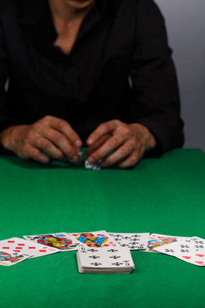 reckless: Gambling man in black shirt sitting at the table with greencloth and cards on it holding dices in hands.