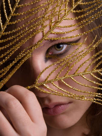 Young beautiful woman with black and gold eyeliner make-up looking through holded in hand golden feather. Close up. Stock Photo