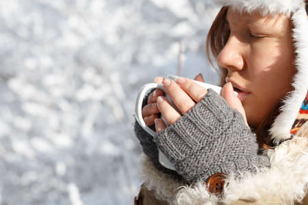 flaps: Beautiful young woman in gray fingerless knitted mittens, cap with ear flaps and coat with white fur drinking tea or coffee holding white cup in hands at the background of snowy forest.