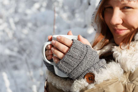 Beautiful young smiling woman in gray fingerless knitted mittens and coat with white fur holding in hands white cup of tea or coffee at the background of snowy forest.