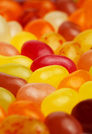 Beautiful colorful background of scattering tasty jelly sugar candies with bright icing. Shallow dof.