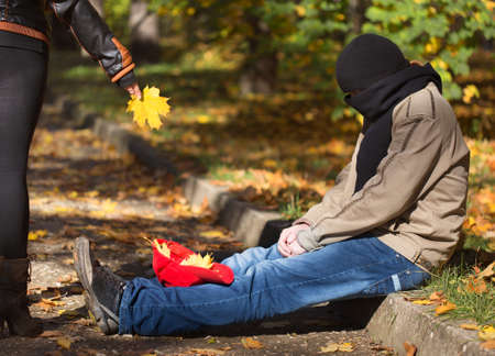 Woman drops yellow leaf in cap of tramp man sitting at the ground and begging in autumnal park with face closed in scarf
