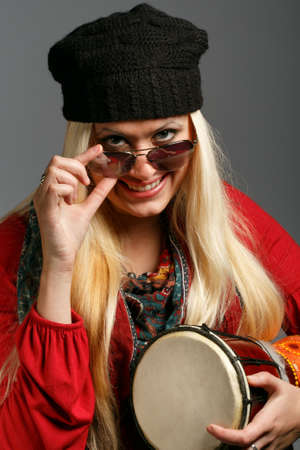 djembe drum: Young beautiful smiling blonde woman in colorful clothes, black hat and sunglasses with a cheerful look holding small ethnic djembe drum at grey background
