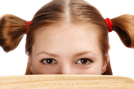 ponytails: Beautiful female face with funny ponytails tied by red scrunchies hidden behind wooden board isolated on white background. Close up.