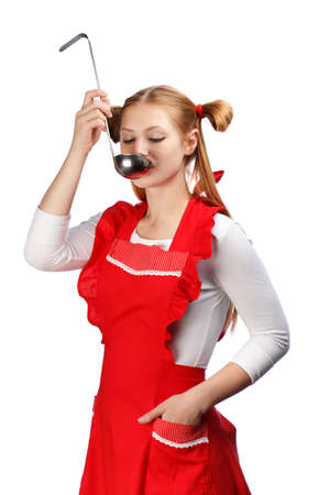 ponytails: Young beautiful attractive housewife in bright red apron with funny ponytails tasting meal from ladle isolated on white background.