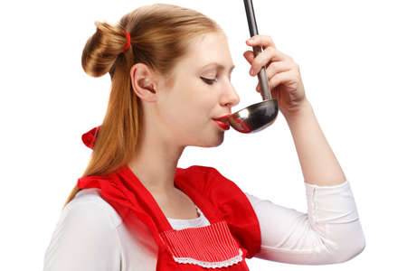 ponytails: Young beautiful attractive housewife in bright red apron with funny ponytails tasting meal from ladle isolated on white background. Close up. Stock Photo