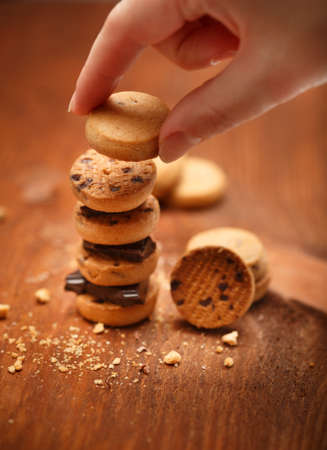 Elegant female hand puts small bisqiut cookies on each other with chocolate pieces between and makes turret at wooden table background with chips scattered around. Shallow dof. Focus on fingers.