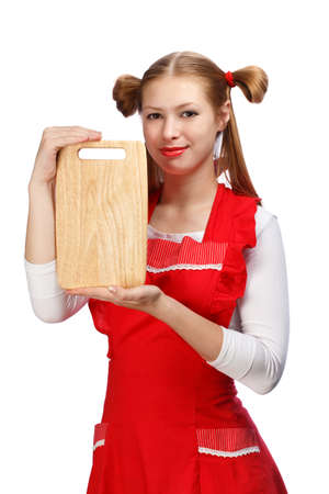 ponytails: Young beautiful attractive smiling housewife in bright red apron with funny ponytails holding rectangular wooden cutting board isolated on white background.