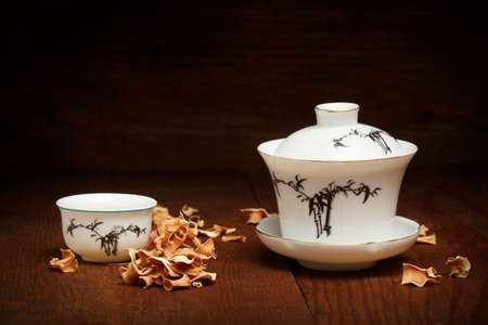 lemongrass tea: Beautiful porcelain set for chinese tea ceremony of white gaiwan and cup standing at brown wooden table with dried lemongrass scattered around Stock Photo