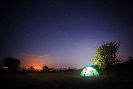 tent city: Tourist tent stands on glade under starry night sky and shines from within with city lights glow at the horizon.