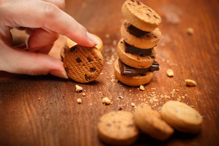 turret: Elegant female hand holds small bisqiut with cookies and chocolate pieces turret near at wooden table background with chips scattered around. Shallow dof. Focus on hand with cookie. Stock Photo