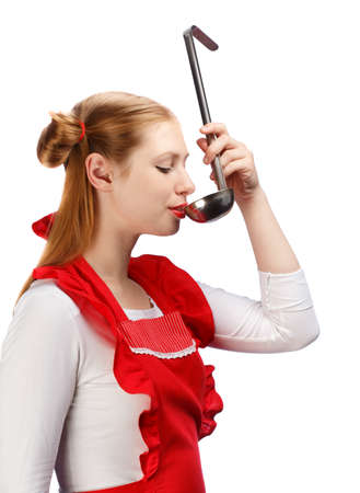 ponytails: Young beautiful attractive housewife in bright red apron with funny ponytails tasting meal from metal ladle isolated on white background. Stock Photo