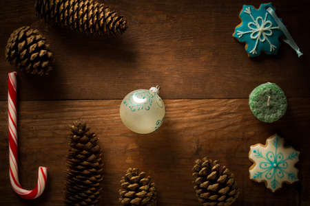 bisquit: Beautiful christmas frame decoration from peppermint candy cane stick, christmas ball, candle, showflake shaped and patterned bisquit cookies, fir cones and pinecones at brown wooden background.