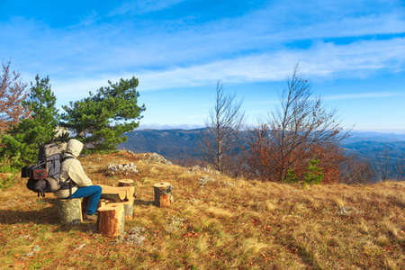 Traveller man with a backpack sits on a tree stump and admires autumnal landscape background with dry grass, orange leaves, blue cloudy sky and mountains at the horizon. Stock Photo