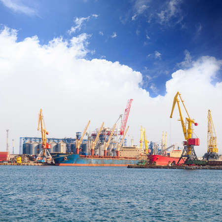 lading: Bright yellow, red and orange cranes and freighters stand in the dock at the port harbor near the sea under blue cloudy sky. Odessa, Ukraine. Stock Photo