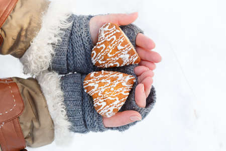 Female hands in knitted grey mittens hold beautiful heart shaped biscuit cookies with white icing at snow background. Focus on cookies. Top view.
