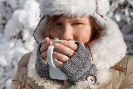 flaps: Young woman in grey fingerless knitted mittens, cap with ear flaps and coat with white fur drinks from cup in hands at the background of snowy forest. Shallow dof. Focus on hands with cup.