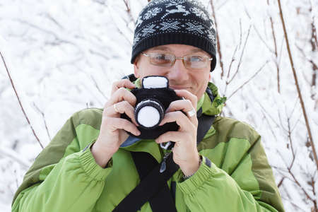 Young smiling man in glasses, green sports jacket and ornamented hat stands in winter forest with knitted toy photographic camera in hands. Shallow dof. Focus on hands. Stock Photo