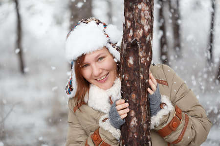 flaps: Young beautiful smiling woman in coat with white fur, hat with ear flaps and grey fingerless knitted mittens hugs a tree in winter forest with falling snow around. Shallow dof. Focus on eyes.