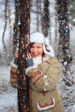 Young beautiful smiling woman in coat with white fur, hat with ear flaps and grey fingerless knitted mittens hugs a tree in winter forest with falling snow around. Stock Photo