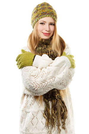 Young stylish smiling blonde woman in variegated melange knitted hat, scarf with fringe, mittens and long patterned white sweater stands isolated on white background.