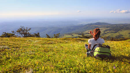 Young female traveller with backpack and long brown hair sitting at green grass glade and making photo of mountain lanscape in summer day under blue sky Stock Photo