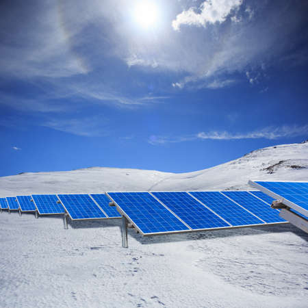 Beautiful modern solar station with blue panels standing in winter field with white snow and hills at the horizon under bright cloudy sky with sunlight.