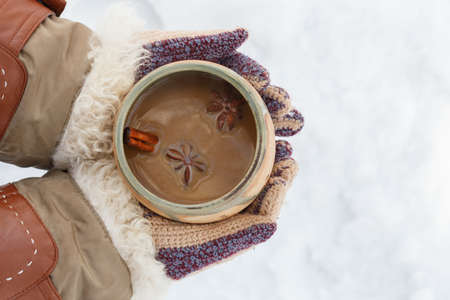 Female hands in knitted grey mittens hold white cup of spicy coffee with anisetree star. Top view. Stock Photo